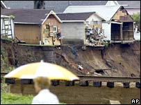 Homes perch on the edge of a bank washed away by floods in Minnesota