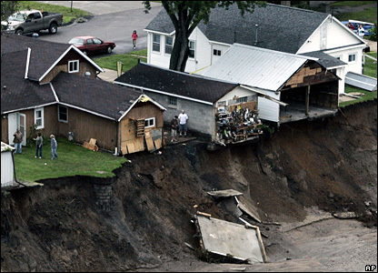 Houses are perched over a deep gulley caused by flooding in Winona, Minnesota