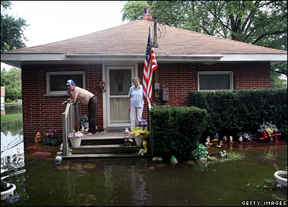 A couple stand on the front steps of their home surrounded by flood water in Fox Lake, Illinois