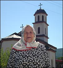 Fata Orlovic next to the church on her front yard, August 2007