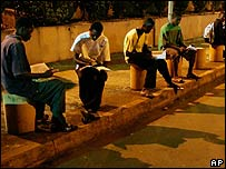 Young Guineans study under the dim parking lot lights