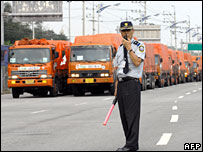 A man talks on a radio as South Korea trucks carrying aid wait to cross into North Korea on 23 August 2007