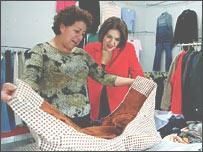 Alicia Hernández muestra a Mary Ellen Iskenderian (izq.) la ropa que hace.