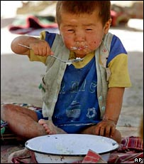 Tajik toddler feeds himself porridge, where a severe drought has devastated crops