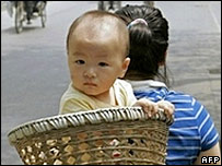A mother cycles with her baby in Beijing, China