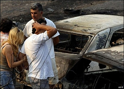 People survey burned out cars near Zaharo, in western Greece