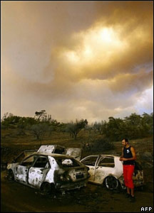 A man surveys burned out cars near Artemida, in western Greece