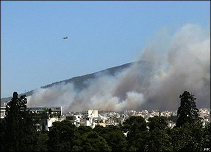 A plane drops water over burning parts of Athens