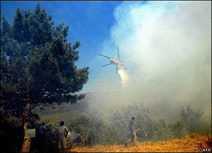 A helicopter drops water on a fire on Mount Taygete in the Peloponnese in southern Greece