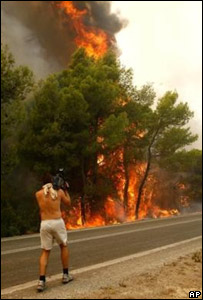 A cameraman gets close to the flames in Zaharo, Greece