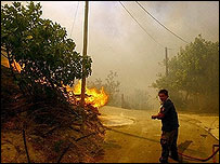 A fireman tries to approach burning houses near Zaharo in Greece