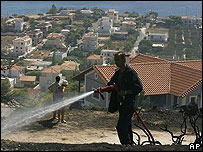 A fireman douses a fire in Greece