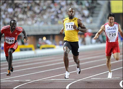 Asafa Powell qualifies in second place in the first men's 100m semi-final, between Trinidad and Tobago's Marc Burns (L) and Japan's Nobuharu Asahara