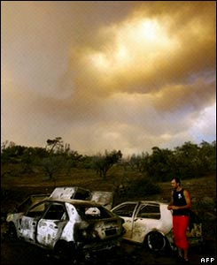 A man looks at burnt cars left by villagers trying to escape the fire in the village of Artemida in Zacharo.