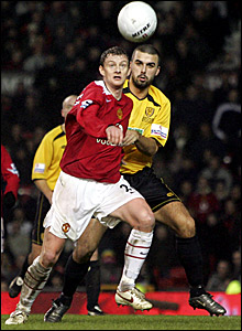 Ole Gunnar Solskjaer (left) challenges Burton's Ryan Austin for the ball