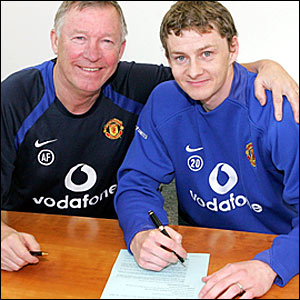 Ole Gunnar Solskjaer (right) signs his new contract, accompanied by manager Sir Alex Ferguson