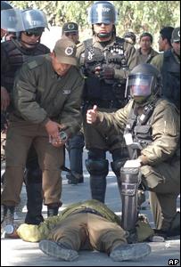 Dos miembros de las fuerzas de seguridad atienden a un compañero herido por la turba