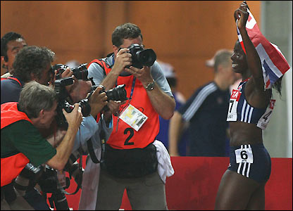 A large crowd of press photographers follow Ohuruogu on her lap of honour