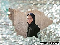 An Iraqi girl walks past glass shattered after clashes between US forces and militias in a Mehdi Army stronghold