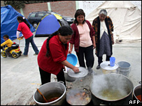A family in Pisco cooks on the street