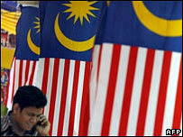 A man walks past Malaysian flags