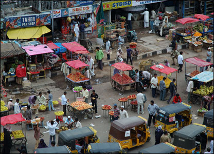 The organised chaos of traffic, fruit sellers, pedestrians and shopkeepers operating within a confined space as seen from the Charminar, Hyderabad.