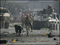 Investigators check the scene after a suicide attack near Kabul airport