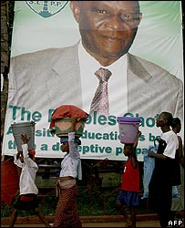 Women walk past a poster of SLPP's Solomon Ekuma Berewa