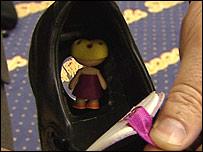 The doll is hidden in the heel of the shoe