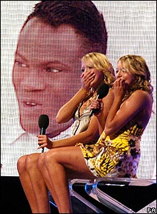 Big Brother winner Brian on screen behind twins Sam and Amanda