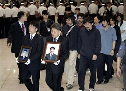 Relatives of dead hostages carrying pictures, followed by freed hostages