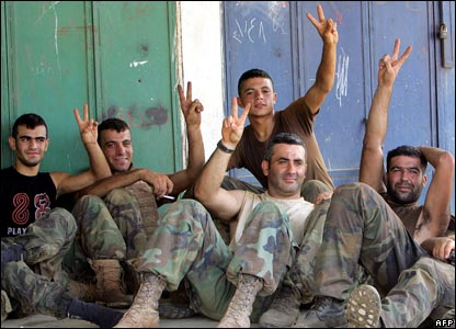 Lebanese soldiers make the victory sign as they rest outside in an area next to the besieged Palestinian refugee camp of Nahr al-Bared