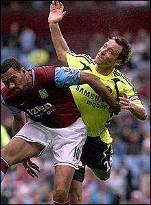Aston Villa's John Carew and Chelsea's John Terry battle for the ball