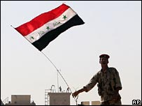 Iraqi soldier waving flag at Basra palace