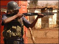 Police officer firing rubber bullets in Soweto, 3 September 2007