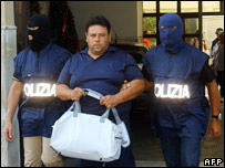 A member of the Mafia is escorted out of police headquarters in Palermo [File pic]