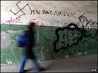 "Student walking past Russian graffiti reading ""We love you"" with a swastika mocking foreigners"