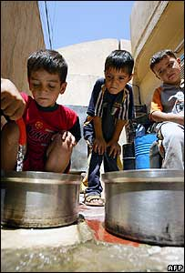 An Iraqi boy fills a pot with water at his home in Baghdad's predominantly Shia suburb of Sadr City, 7 August 2007