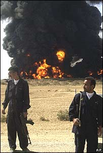 Iraqi policemen stand near a burning oil pipeline blown up by insurgents, 23 September 2004