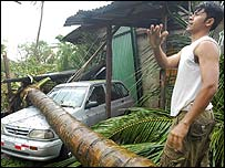 A man stands next to where a palm tree fell on a car in Puerto Cabezas, Nicaragua