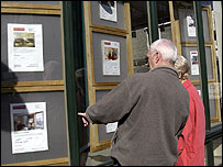 People look at an estate agent's window