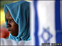 A Sudanese refugee stands behind an Israeli flag