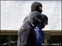 German security officials flank one of three terrorist suspects (C) as he is lead from a helicopter to Karlsruhe's federal court