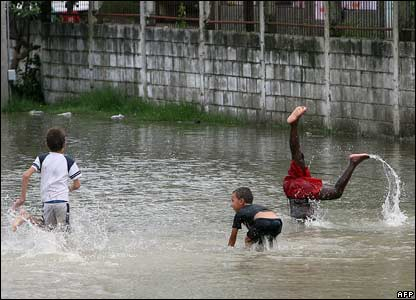 Children play in a flooded football field in San Pedro Sula, Honduras
