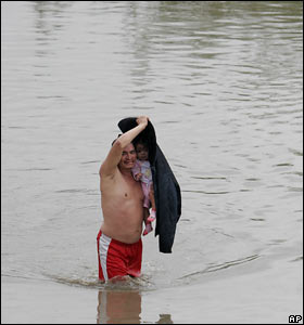 A man carries a child in floods in San Pedro Sula, north-eastern Honduras