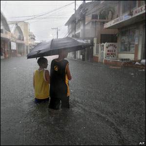 People shelter under an umbrella in a flooded street