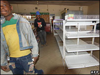 Shoppers walk past empty shelves (Demond Kwande/AFP/Getty Images)