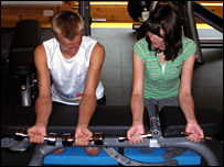 Heikki Kovalainen shows Sarah how in the gym