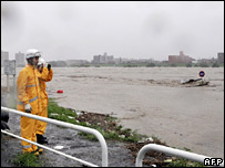 A firefighter looks at the swollen Tama river near Tokyo on 7 September 2007