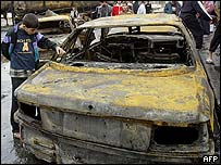 Boy walks past a burned-out car following a bomb attack in Amin
